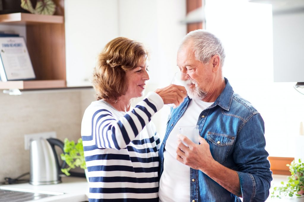 Senior couple drinking water at home.